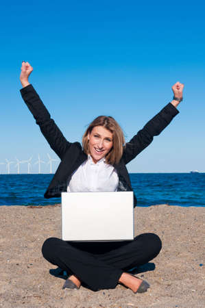Happy successful business woman working with laptop on the beach on sunny day, vertical photo