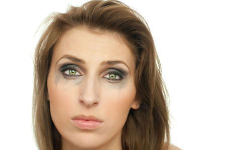 portrait of young beautiful crying woman with leaking makeup and green eyes on white, isolated, copyspace, high key photo