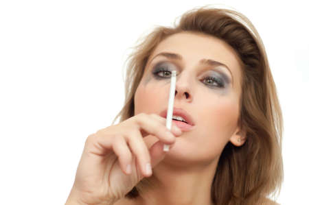portrait of young beautiful crying and smoking woman with leaking makeup on white, isolated, copyspace, looking on cigarette