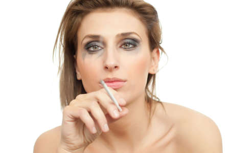 portrait of young beautiful crying and smoking woman with leaking makeup and cigarette on white, isolated, copyspace, looking aside