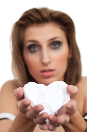 portrait of young beautiful crying woman giving paper heart, leaking makeup, isolated, copyspace, vertical, out of focus Stock Photo