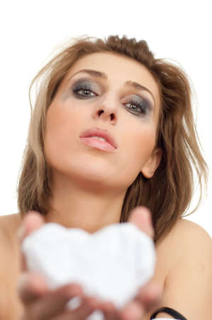 portrait of young beautiful crying woman giving paper heart, leaking makeup on white, isolated, copyspace, vertical