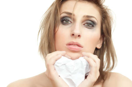 portrait of young beautiful crying woman with paper heart and leaking makeup on white, isolated, copyspace, close