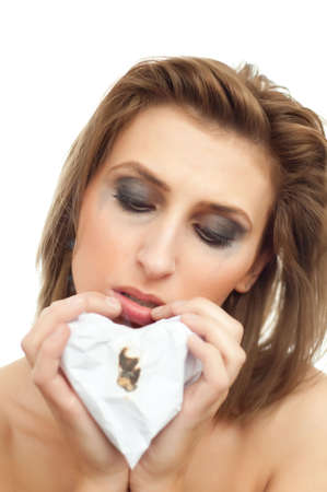 portrait of young beautiful crying woman with paper heart and leaking makeup on white, isolated, copyspace, looking down
