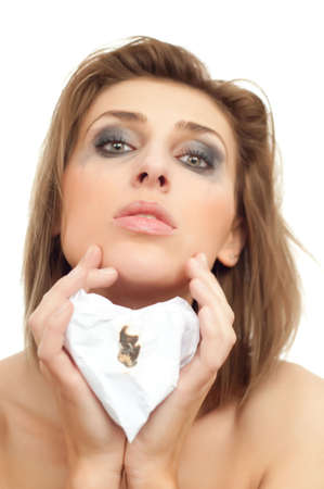 portrait of young beautiful sad woman with burning paper heart and leaking makeup on white, isolated, copyspace, vertical