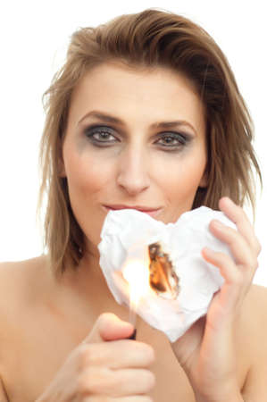 portrait of young beautiful happy woman with burning paper heart and leaking makeup on white, isolated, copyspace Stock Photo