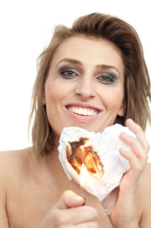 portrait of young beautiful smiling woman with burning paper heart and leaking makeup on white, isolated, copyspace, vertical Stock Photo