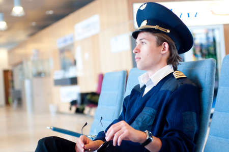 young pilot sitting in the airport on blue chair, close