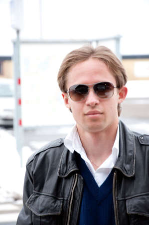 portrait of young man wearing sun glasses and leather jacket on the street Stock Photo