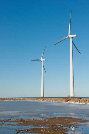 Two windmills near seaside with reflection in the lake, vertical, copenhagen, oresund, denmark