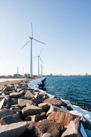Windmills near seaside covered with big stones, vertical, copenhagen, oresund, denmark