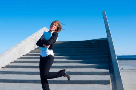 woman stairs: business woman laughing on the stairs with laptop on sunny day, wide