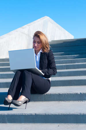 woman stairs: business woman sitting on the stairs with laptop on sunny day Stock Photo