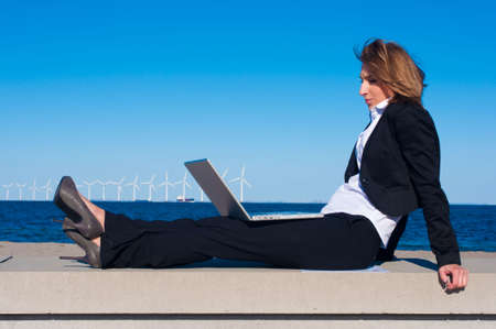 business woman relaxing with laptop on the beach on sunny day Stock Photo