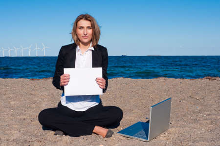 business woman sitting on the sand with laptop on the beach on sunny day, copyspace, vertical photo