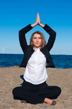 business woman sitting in yoga pose on the beach on sunny day