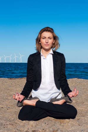 business woman sitting in lotus pose on the beach on sunny day