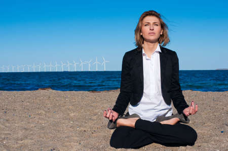business woman sitting in lotus pose on the beach on sunny day, horizontal