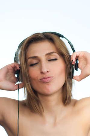 Girl listening music in large headphones on white background, vertical