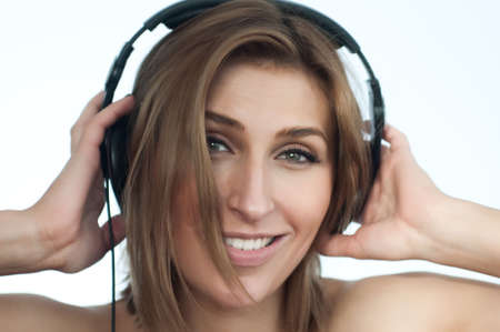Girl listening music holding large headphones on white background, looking in the camera Stock Photo