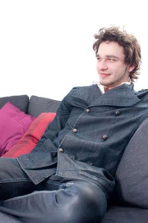 Good looking smiling male model sitting ona sofa isolated