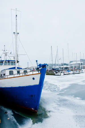Yachts and boats, loaded with snow, waiting for the summer at frozen port Stock Photo