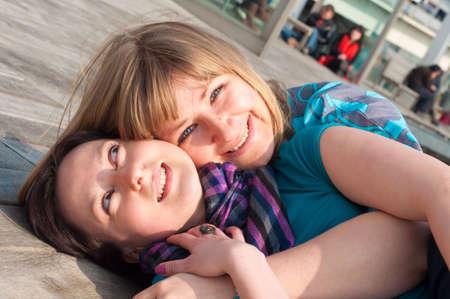 Portrait of two girls having fun and lying on a deck near the Rambla de Mar footbridge in Barcelona,Spain