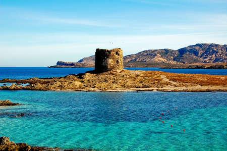 Old stone tower on a small island on Sardinia Stock Photo
