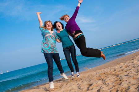 Three girls jump at the beach Stock Photo