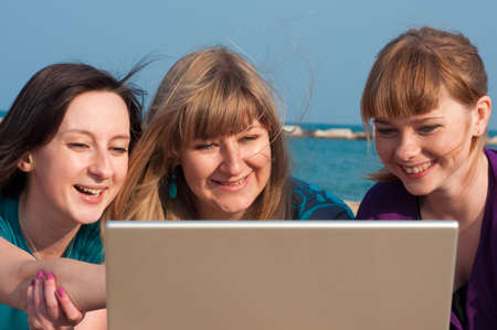 Three girls with a laptop on a beach