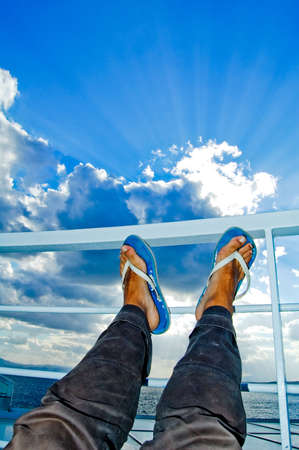 Two feet pointing to the sun with blue and cloudy sky