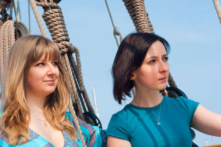 Portrait of two girls posing  on a sailboat photo
