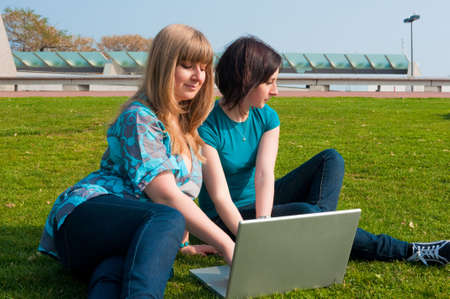 Two girls with a laptop on the grass at sunny day