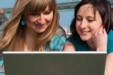 Two girls with a laptop on a beach