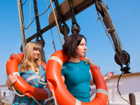 Two girls with a lifebuoy on a ship