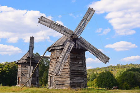 Old wooden windmills on background of blue sky photo