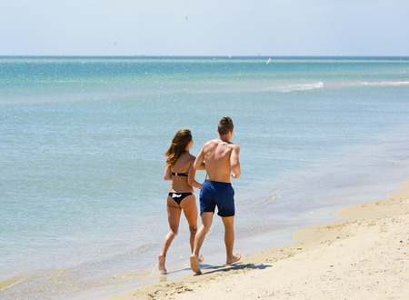 stroll: Couple of young people running or jogging on the beach. Young tanned happy man and woman enjoying vacation in the summer and sea, and stroll on the beach