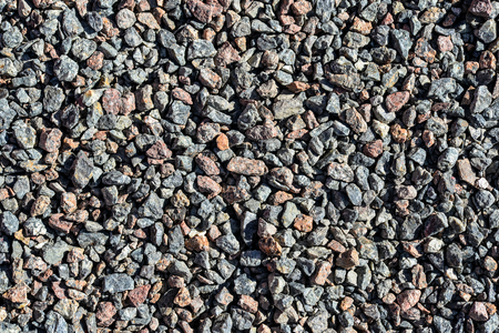 Granite gravel. Brown and gray crushed rocks for construction on the ground. Gravel macadam road texture or background. Template or mock up Standard-Bild - 101750491
