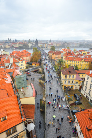 Prague, Czech Republic - October 12, 2017: Ancient Charles Bridge crosses the Vltava river in Prague, Czech Republic. Tourists are walking along Charles Bridge and enjoying the golden autumn and Prague Standard-Bild - 103888396