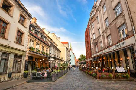 Riga, Latvia - August 23, 2017: Beautiful view on old colorful buildings and street cafes of Riga, Latvia. Summer Riga city center and walking people. Riga architecture. Editorial