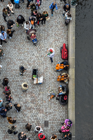 Prague, Czech Republic - October 7, 2017: Top view on crowd, bridge and river. People walking Charles Bridge and listen to street musician in Prague. Standard-Bild - 109600150