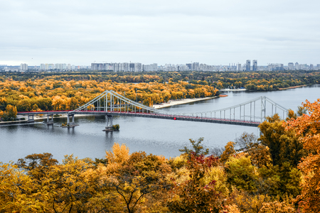 Kiev, Ukraine - October 10, 2018: Golden autumn in Kiev, Ukrain. View on footbridge, river Dnieper and Trukhanov Island in Kyiv. Standard-Bild - 110720377
