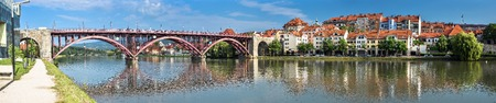 Maribor, Slovenia - May 20, 2018: Panoramic view of Maribor city, Slovenia, Drava River, bridge, old buildings and mountains of Maribor city center. 新聞圖片