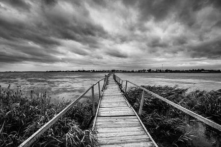 Beautiful summer view on beautiful lake, long wooden bridge and dramatic sky. Serene lake and a bridge without people. Landscape. Destination concept. Black and white photo