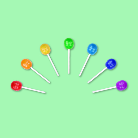 Set of colorful lollipops grouped in a half circle isolated on green background. Candy on a stick. Food background. Flat lay.