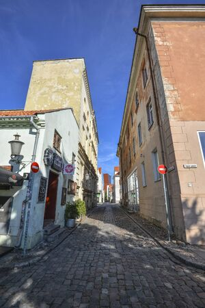 Klaipeda, Lithuania - August 16, 2017: Facades of Old stone houses in the center of Klaipeda town and road from paving stones. Klaipeda city center.