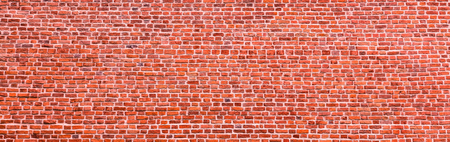 Brick wall, wide panorama of bright red masonry. Wall with small Bricks. Modern wallpaper design for web or graphic art projects. Abstract template or mock up.
