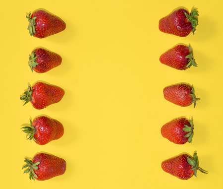Fresh Strawberries close up. Strawberries isolated on bright yellow background with free space. Frame, template or mock up. Flat lay.