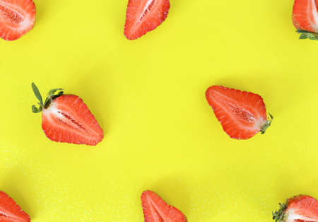 Strawberries pattern close up. Bright pattern of fresh cut in half strawberries on yellow background. Top view, flat lay.