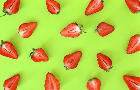 Strawberries pattern close up. Bright pattern of fresh cut in half strawberries on light green background. Top view, flat lay.